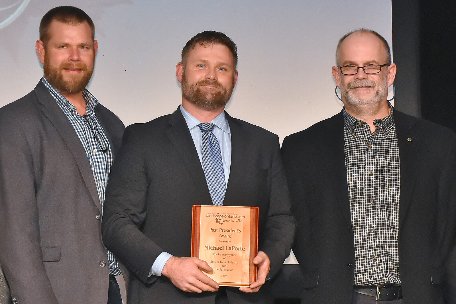 Michael LaPorte (centre), accepts the 2019 Past President's Award.