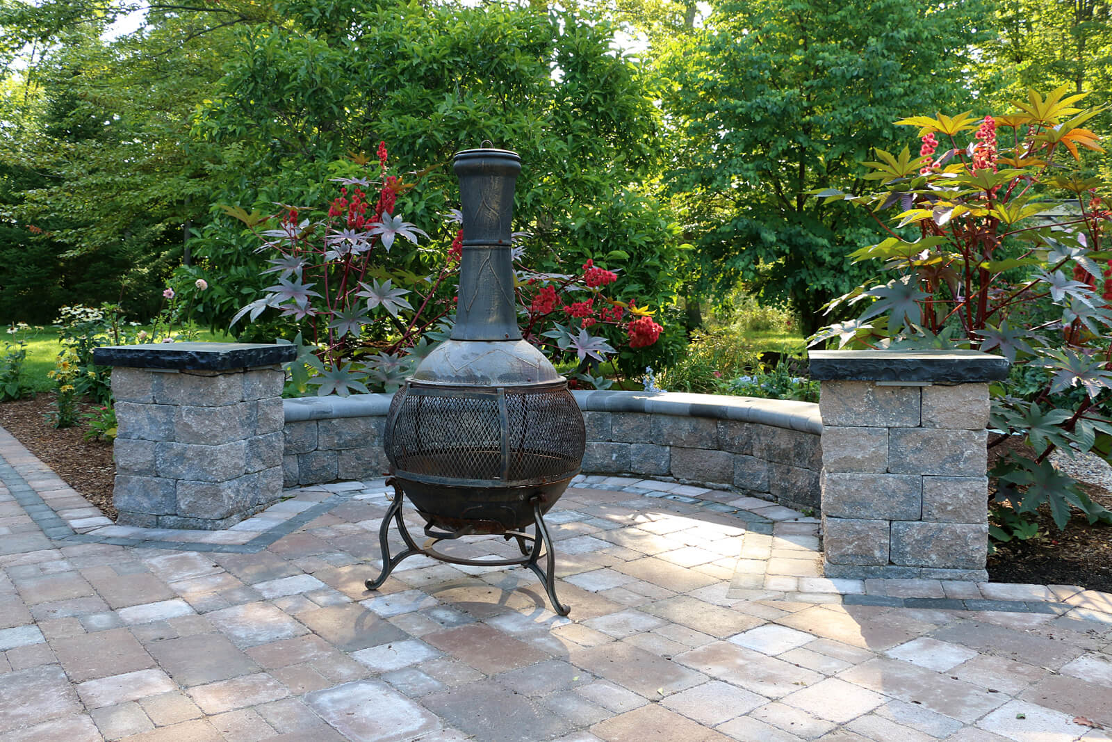 stone patio area with retaining wall and black chiminea