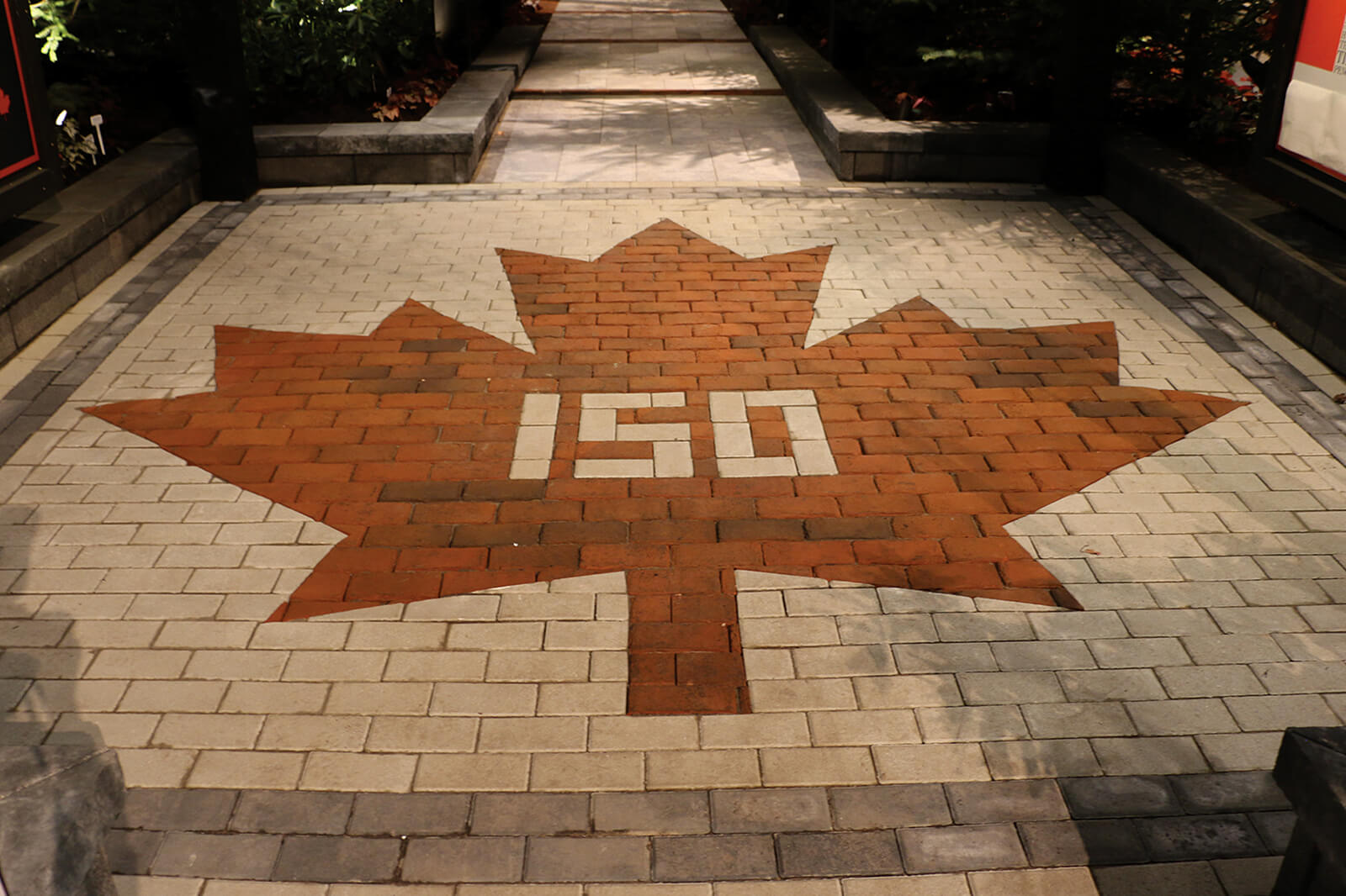 interlocking stone with a red maple leaf pattern and 150 in the centre