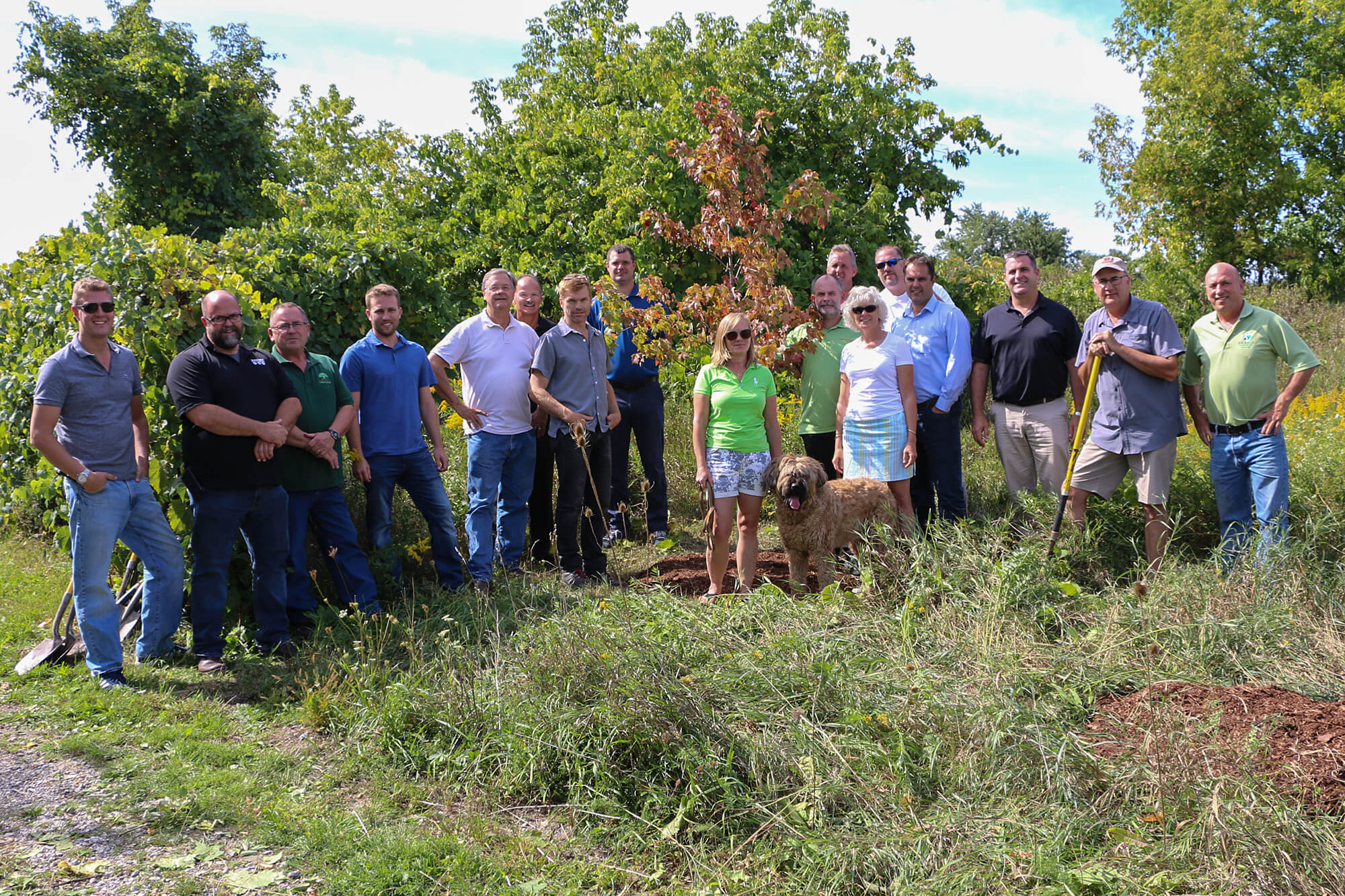 LO boar members surround a newly planted tree