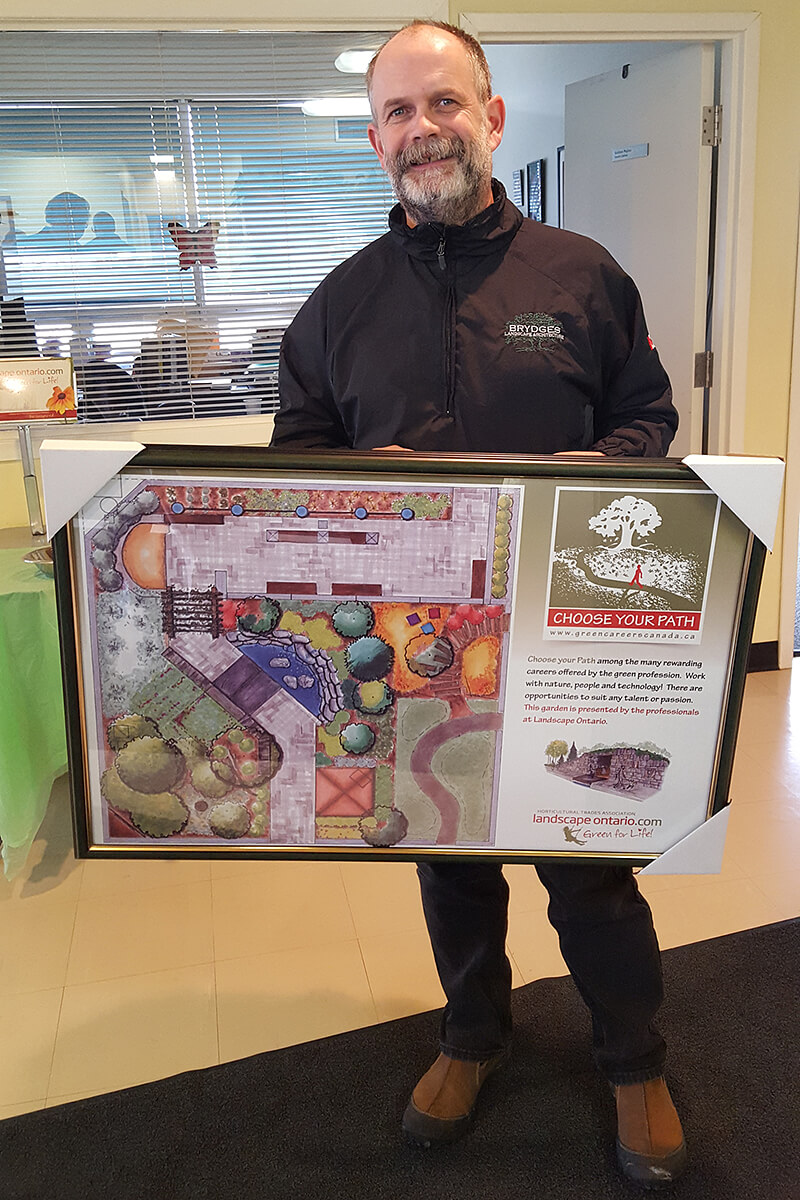 paul brydges holding a framed print of his garden design