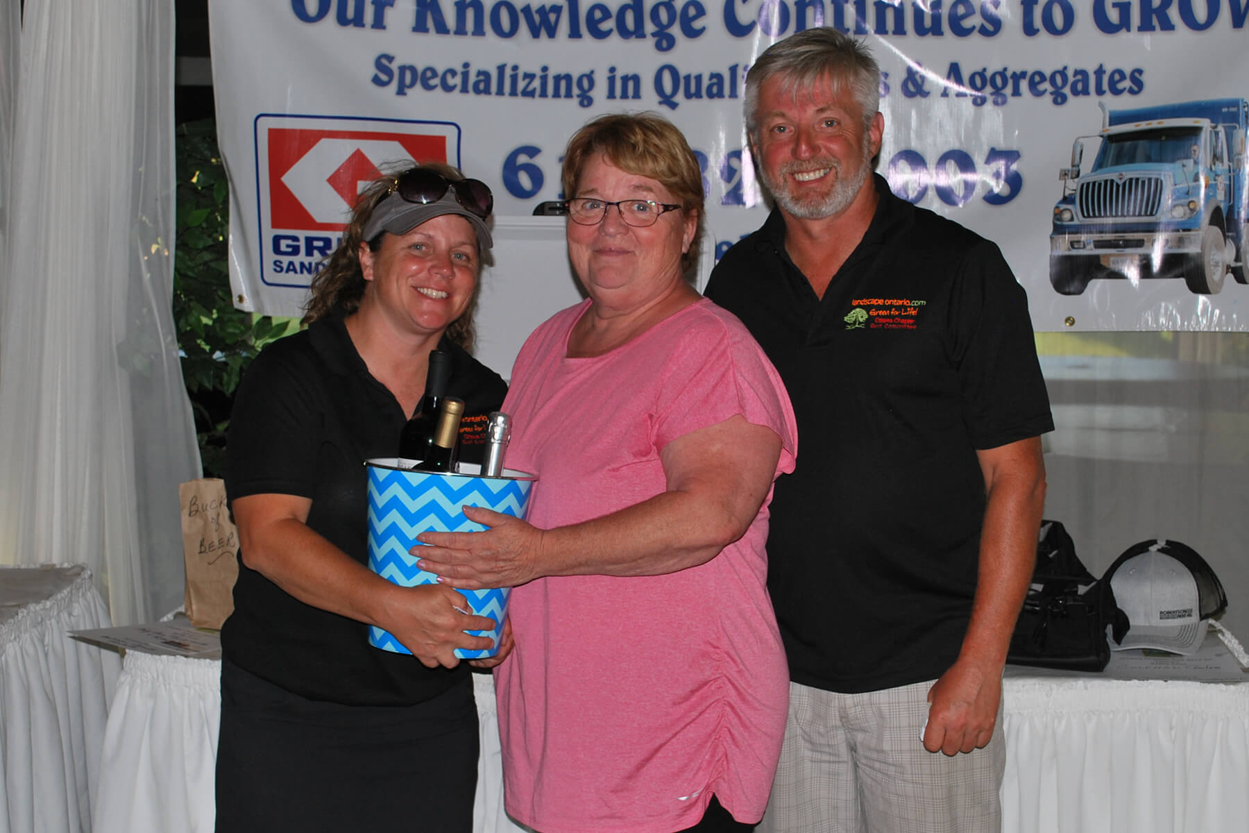woman accepting a prize from two representatives at a golf tournament