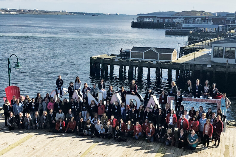 a large group of women posing for a photo on a pier in halifax