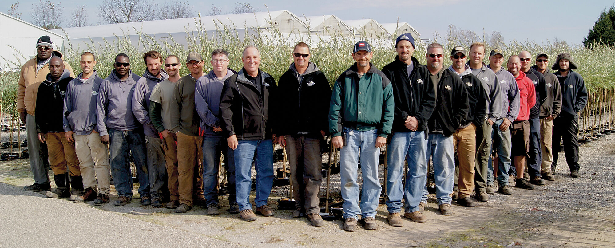 large group of workers standing in a nursery field