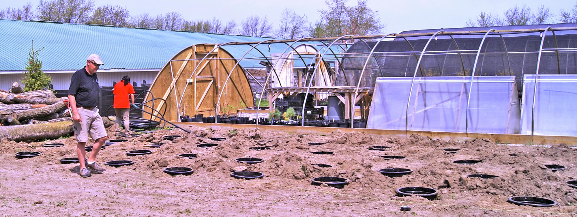hoop house with pots in the ground beside it