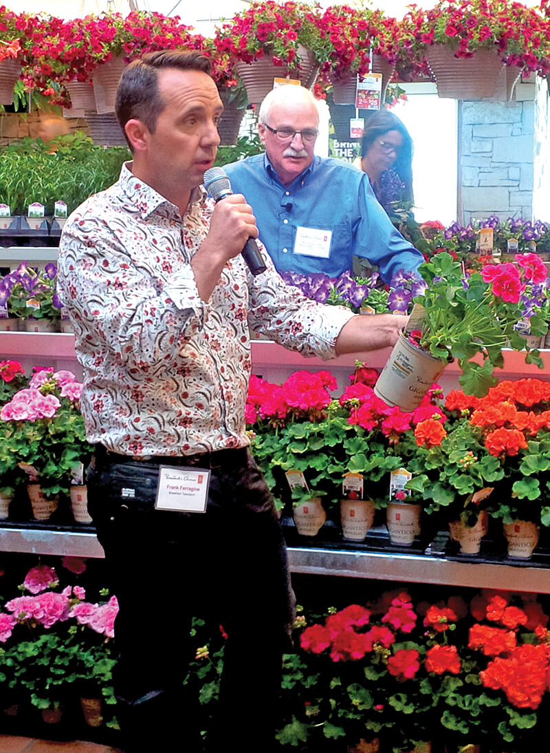 man with microphone speaking in a greenhouse full of plants