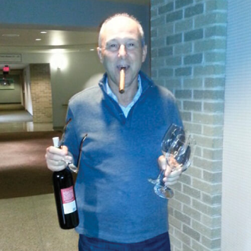 man holding bottle of wine and glasses