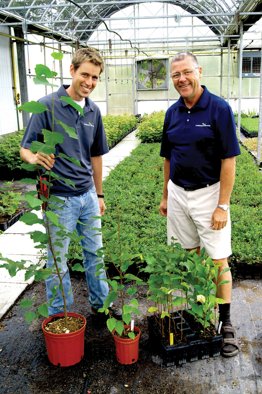 two men in a greenhouse showing off plants