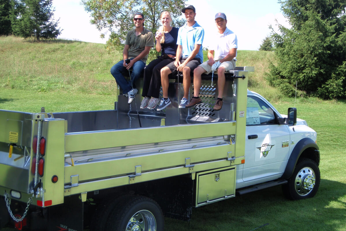 four people sitting in the back of a dump box truck