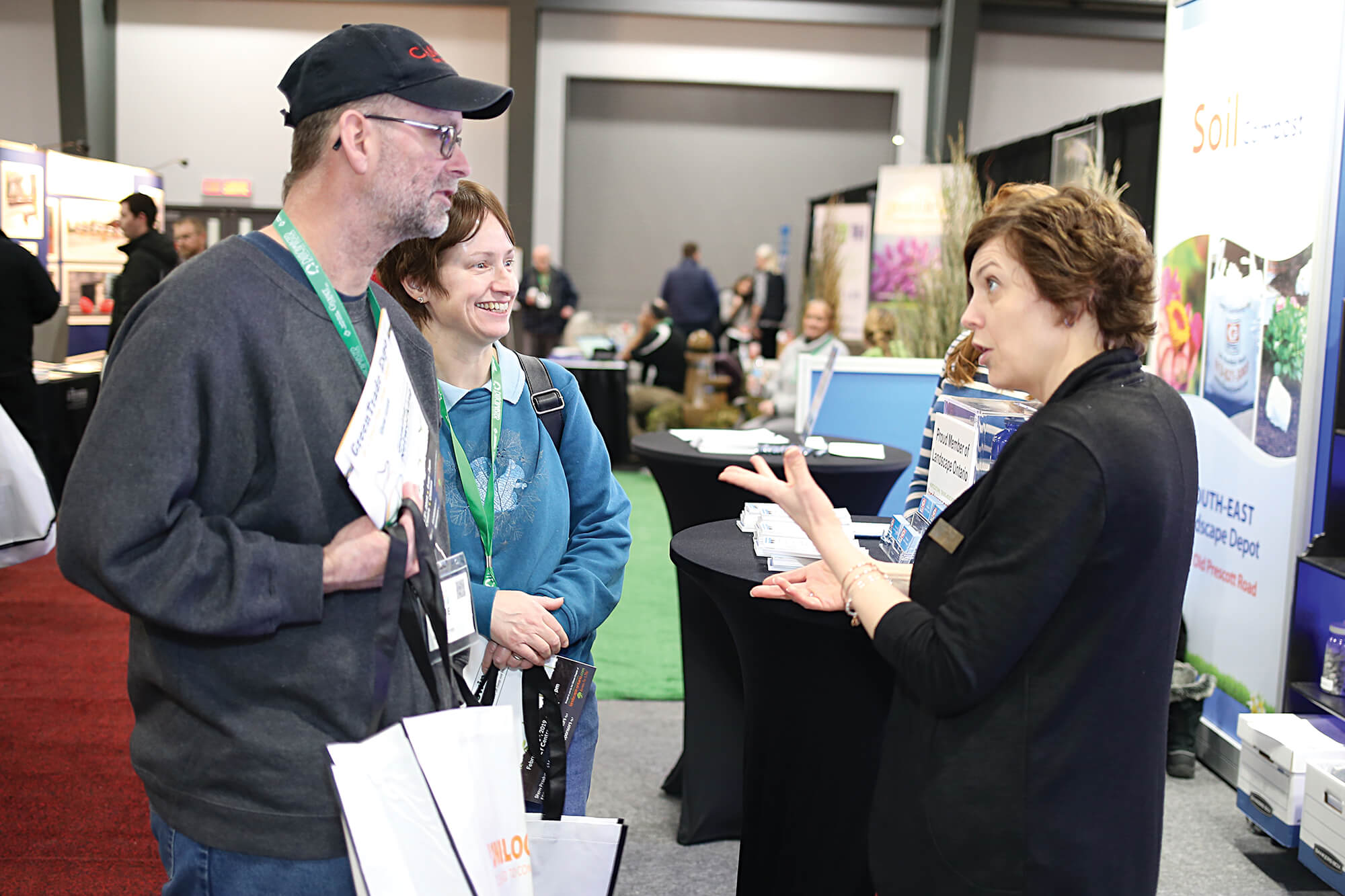 man and woman talking with an exhibitor at a trade sho
